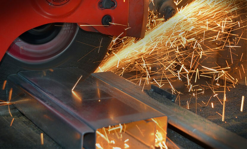 A custom fabrication professional is sawing a sheet of metal